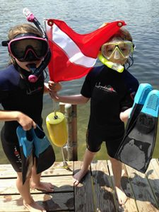 Image of Two Children with Masks & Snorkels On and Fins and Dive Fins In Hands